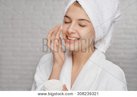 Beautiful, Pretty, Young Woman Applying On Face Cream For Skin Care. Girl In White Bathrobe With Tow
