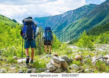 Hiking In Mountains. Men Hike In Mountain Trail. Tourists With Backpacks Walking On Trek. Active Lei
