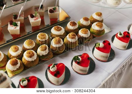 White And Chocolate Desserts With Fruits And Crem,  Cupcakes On Stand, Modern Sweet Table At Wedding