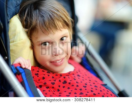 Portrait Of A Cute Little Disabled Girl In A Wheelchair. Child Cerebral Palsy. Inclusion. Family Wit