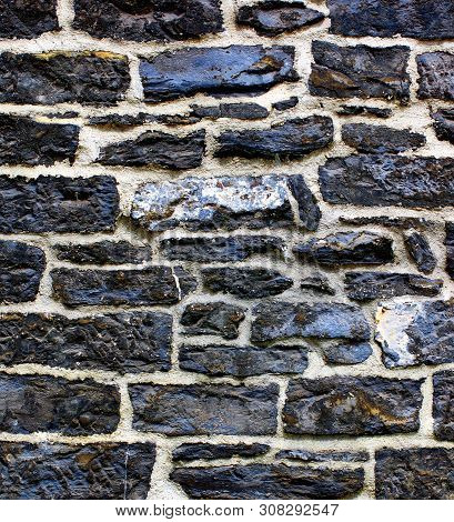 Background Of Black And Grey Old Wall Stones With Cracked Surface And Concrete Closeup Outdoors