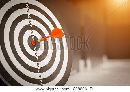 Red Dart Arrow Hitting In The Target Center Of Dartboard On Bullseye With Sun Light Vintage Style, T
