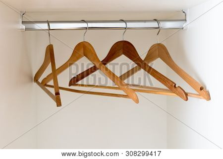 A Horizontal Detail View Of An Empty Metal Coatrack In A White Wardrobe With Four Empty Wooden Coath
