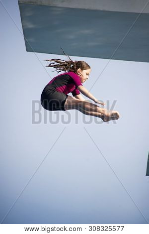 Piked Dive. Little Caucasian Female 8 Years Old Girl In Neoprene Shorty Surfing Wetsuit Diving From