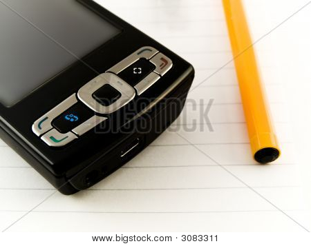Ballpoint Pen And Mobile Phone On Notepad White Background