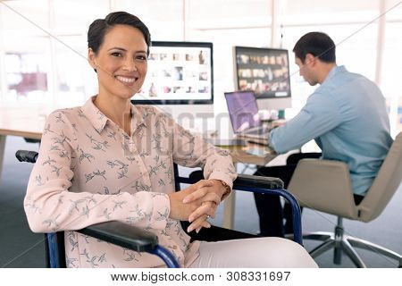 Front view of happy disabled mixed race female graphic designer in wheelchair looking at camera in a modern office. Caucasian man working on the laptop in the background.  poster