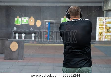 Russia, Kazan - June 23, 2019:man In Shooting Range In Shooting Action With Glock 19, View From Behi