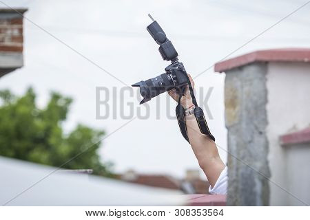Photographer Shoots And Hides Through A Camera Fence. A Paparazo Shot Across A Wall With A Raised Ha