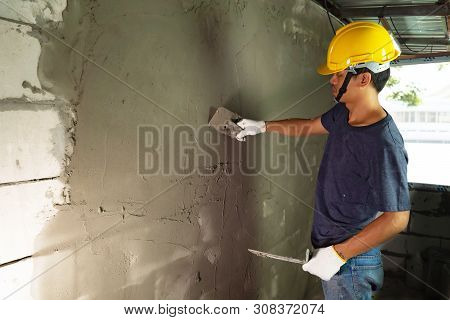 Plasterer In Blue Working Uniform Plastering The Wall Indoors ,plasterer Putting Plaster On Wall