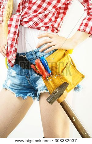Woman wearing protective workwear toolbelt on jeans shorts. Girl working at flat remodeling. Building, repair and renovation. poster