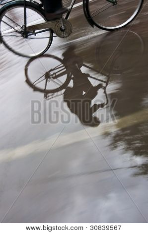 Man on bicycle in puddle