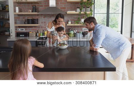 Front view of happy Caucasian family preparing vegetable salad in kitchen at home