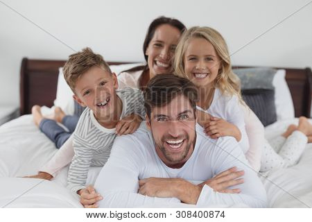 Portrait of Caucasian family lying together on bed in bedroom at home
