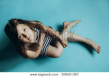 Girl sitting on plain blue background looking at camera. Child glancing up top view. Simple wallpaper, background. Serious and sad facial expression. Kid in striped dress with legs crossed poster