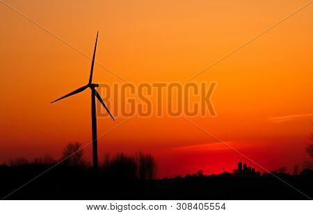 Wind Turbine In The American Midwest. Silhouette Of Large Wind Turbine At Sunset In The Rural Farmla