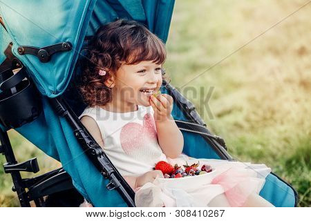 Cute Adorable Caucasian Toddler Baby Girl Sitting In Stroller Outside And Eating Berries Fruits. Fun