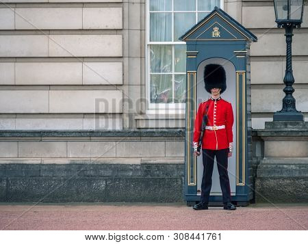 London, Uk - April, 2019: A Guard Standing Outside Buckingham Palace. English Guard Patrolling In Lo