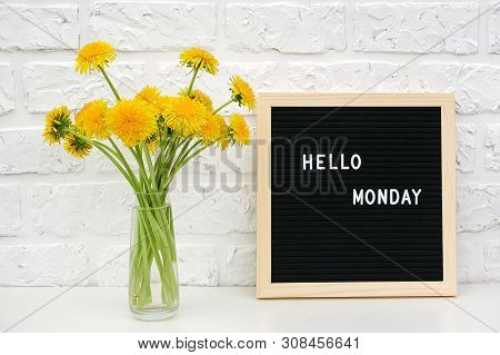 Hello Monday Words On Black Letter Board And Bouquet Of Yellow Dandelions Flowers On Table Against W