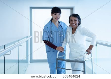 Front view of Asian female doctor with stethoscope around the neck helping mature mixed-race female patient to walk with walker in the corridor at hospital