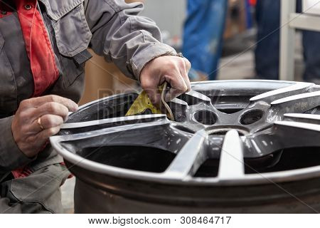 Master Body Repair Man Is Working On Preparing The Surface Of The Aluminum Wheel Of The Car For Subs