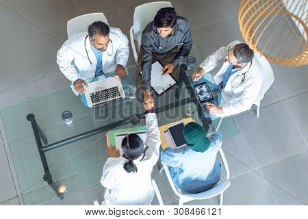 High angle view of diverse medical team working together at table in hospital. Coffee cup, medical folders, clipboard, digital tablet and laptop are on the table.