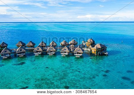 Travel vacation paradise aerial drone video with overwater bungalows in coral reef lagoon sea. Aerial video from Bora Bora, French Polynesia, Tahiti, South Pacific Ocean.
