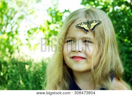 Bright Butterfly Sitting On A Child. Child With A Butterfly. Butterfly Machaon On A Little Girl. Sel