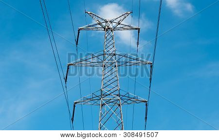 Bottom view of a high-voltage electricity pylon against blue sky with clouds at sunny day. High-voltage power transmission tower. Power engineering. poster