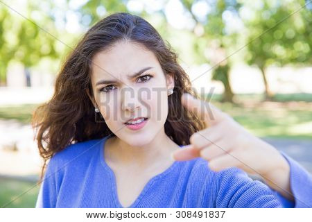 Disappointed Pretty Young Woman Accusing Viewer In Park. Beautiful Lady Looking And Pointing At Came