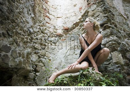 Blonde girl standing on a stone monument