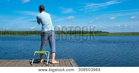 A Man On The Pier, Rear View, Throws A Fishing Rod, Against The Blue Sky And The Lake