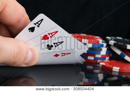A Set Of Top Four Cards, In Hand For Viewing, On A Black Table With Reflection, With A Scattered Bet