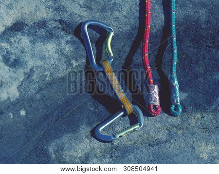 Climbing Equipment - Detail Carabiners And Rope. Ascender Placed On Rock At Old Rope. Hank Sling Car