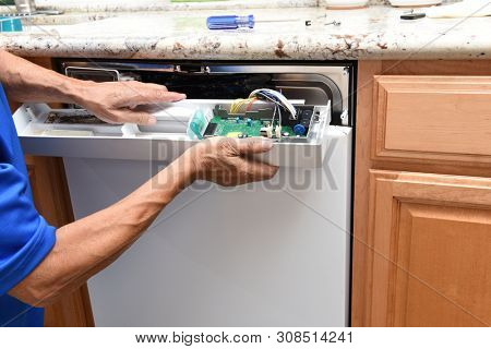 Closeup of a appliance repairman removing the control panel to a broken dishwasher.