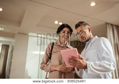 Plastic Surgeon Consulting Client Holding Tablet N Hands