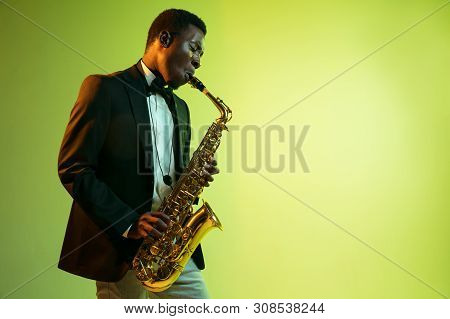Young African-american Jazz Musician Playing The Saxophone On Gradient Yellow-green Studio Backgroun