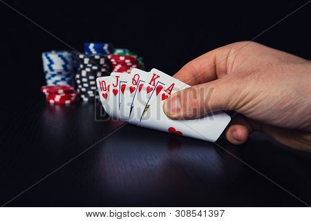 Close Up Hand Of Young Man Poker Player Checking Cautious At His Playing Cards. Betting Chips On The