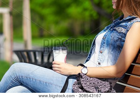 Beautiful And Young Girl Sitting On The Bench. Woman Drinking Coffee And Laughing. Summer
