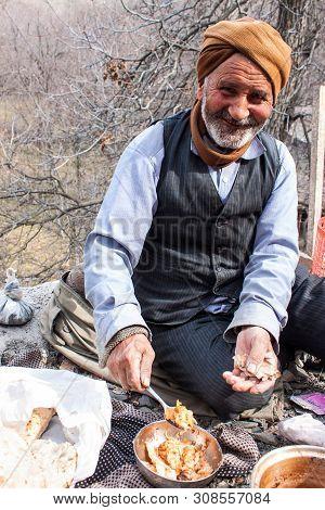 Kang, Iran - February 24: Old Village Man Eats His Lunch On February 24, 2013 In A Village Kang, Ira