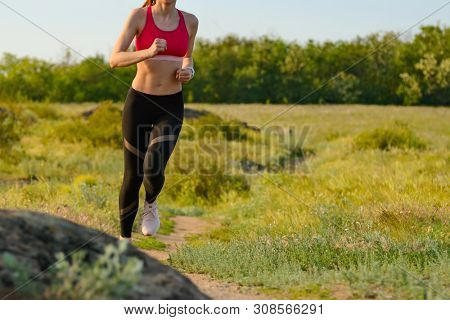 Woman Running on the Mountain Trail in the Hot Summer Evening. Sport and Active Lifestyle Concept.