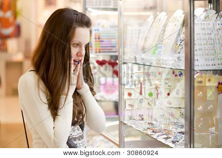Young woman is choosing jewerly in the shop poster