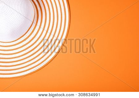 Summer And Vacation Concept. Top View Of Straw Striped Hat On Russet Orange Color Background. Fasion