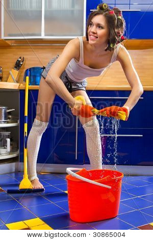 Smiling young woman squeezing floor cloth and cleaning the floor at home