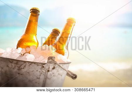 Three Beer Bottles In Metal Bucket Full Of Ice Cubes In The Beach Close Up. Horizontal Composition.