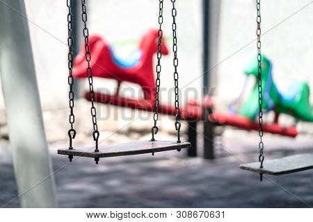 Empty Swing At A Playground. Sad Dramatic Mood For Negative Themes Such As Bullying At School, Child
