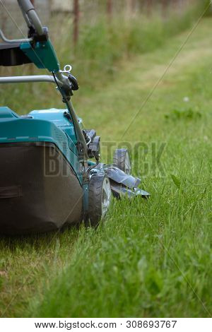 Lawn Mower Cutting Green Grass In Backyard Close Up.