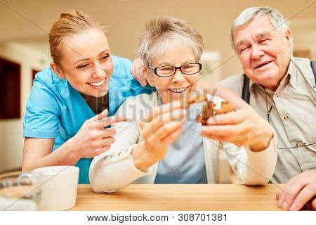 Nursing service Ms. cares for seniors with dementia in a puzzle game with wooden puzzle