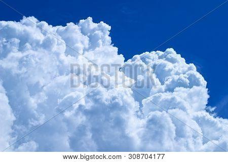 White Puffy Clouds In Blue Sky. A Vertical Shot Of Blue Sky And Puffy White Clouds.