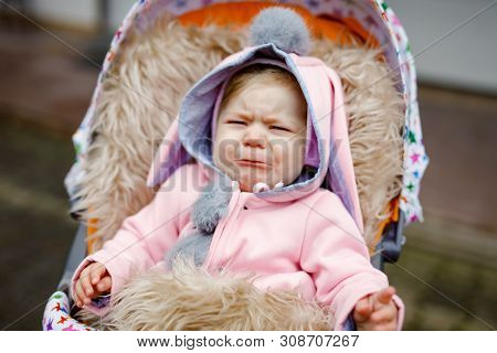 Sad Crying Little Beautiful Baby Girl Sitting In The Pram Or Stroller On Autumn Day. Unhappy Tired A