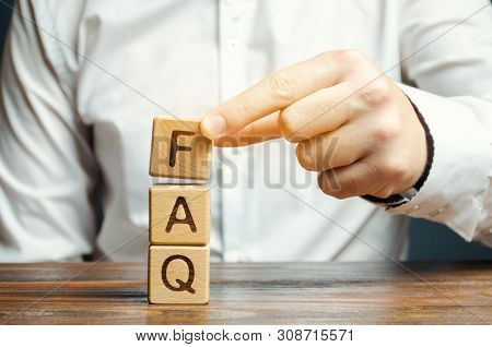 Businessman Puts Wooden Blocks With The Word Faq (frequently Asked Questions). Collection Of Frequen
